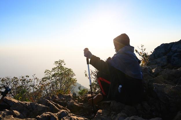 Caminando al hombre que se sienta en la colina en la montaña de la silueta de la puesta del sol con concepto de la aventura de la forma de vida del viaje.