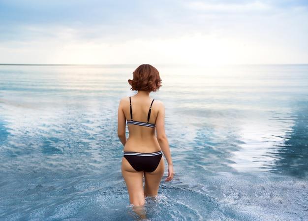 Caminando al mar en el paisaje de verano del patio trasero de la mujer sexy