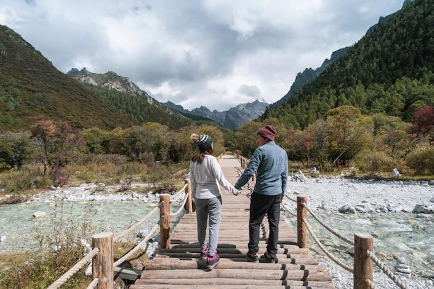 Caminando al viajero joven de la pareja que mira paisaje hermoso en la reserva natural de yading, concepto de la forma de vida del viaje
