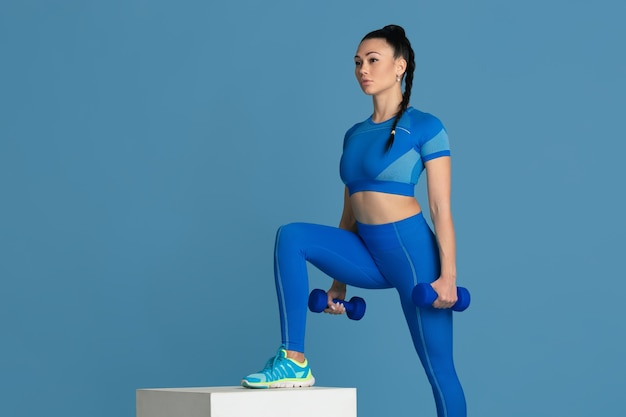 Caminando. hermosa joven atleta practicando en estudio, retrato azul monocromo