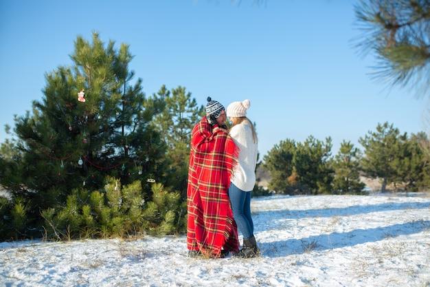 Caminando en el invierno en el bosque, un chico envuelve a su novia en una cálida tela escocesa roja para que se caliente