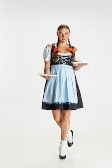 Caminando. retrato de mujer hermosa, camarera en traje tradicional austríaco o bávaro de pie solo aislado sobre fondo blanco. evento de vacaciones, celebración, oktoberfest, concepto de festival.
