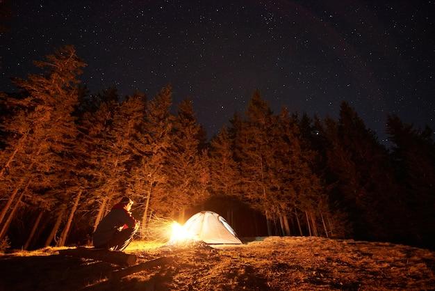 Caminante cerca de fogata y carpa turística en la noche