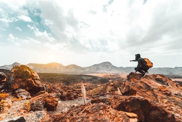 Caminante del éxito que camina en el pico de montaña de la salida del sol que señala al cielo.