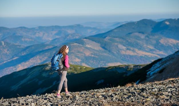 El caminante feliz joven de la mujer está caminando en el plato de la montaña
