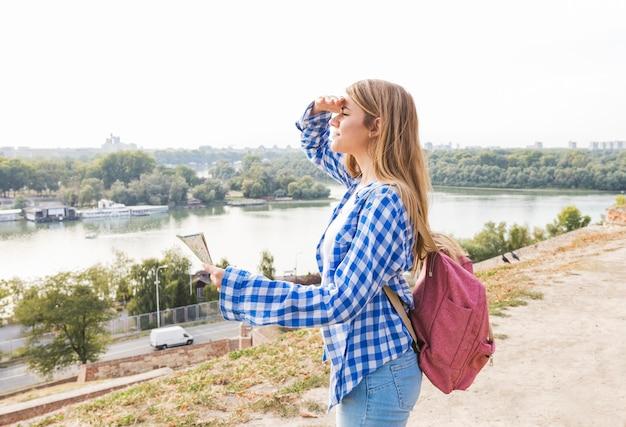Caminante femenino joven con el mapa que protege sus ojos en el aire libre