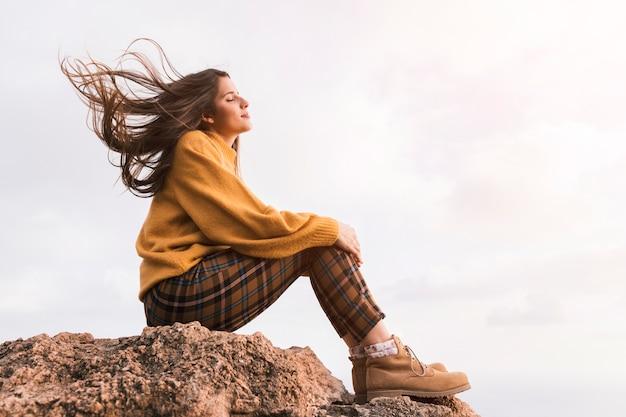 Caminante femenino joven que se sienta encima de la roca que goza del aire fresco contra el cielo