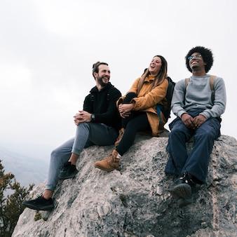 Caminante femenino y masculino joven que se sienta en la roca que goza