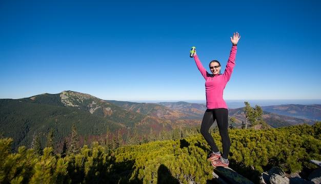 Caminante femenino que alcanza su meta en la cima de la montaña