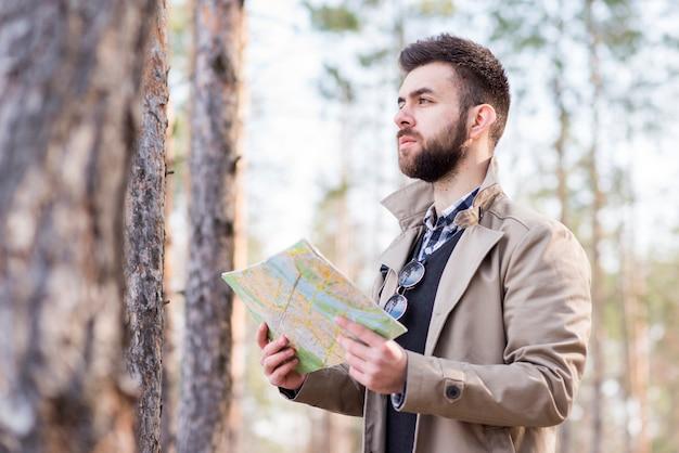 Caminante masculino joven que se coloca en el bosque que sostiene el mapa disponible