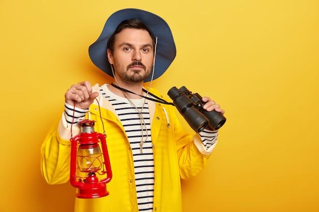 Caminante masculino serio lleva lámpara de gas, usa binoculares durante el viaje de senderismo, vestido con impermeable, mira con confianza a la cámara aislada sobre una pared amarilla