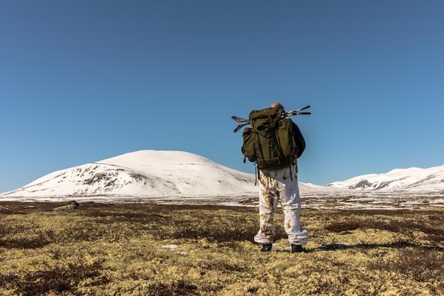 Caminante con mochila grande caminando en las montañas de invierno en dovre, noruega. lado derecho