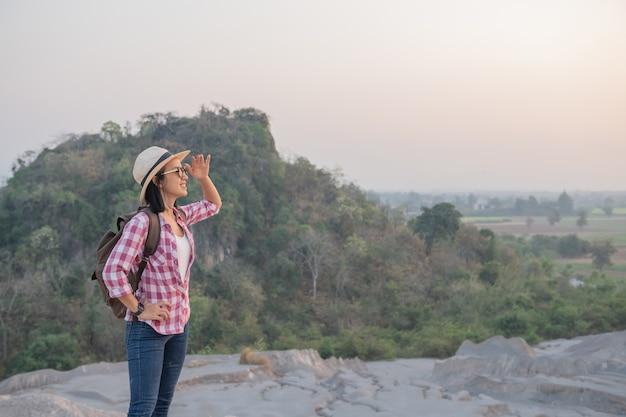 Caminante con mochila de pie en la cima de una montaña y disfrutando de una impresionante vista del valle
