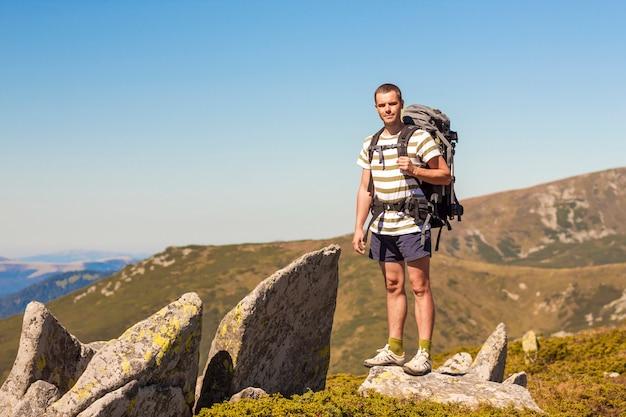 Caminante con mochila de pie en la cima de la montaña.