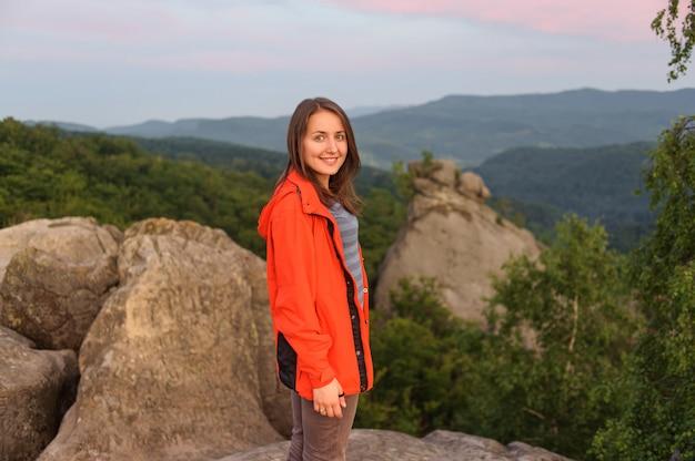 Caminante de la muchacha que se coloca en roca encima de la montaña