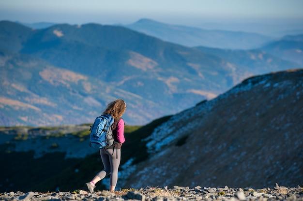 El caminante de la mujer está bajando de la montaña plato