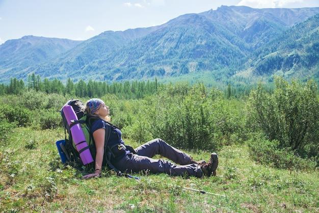 El caminante de la mujer con la mochila que se sienta en hierba verde y la sensación se relajan con los ojos cerrados