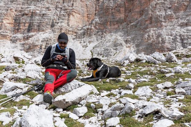 Caminante con su perro descansa sobre el pase y comprueba el mapa en el teléfono inteligente