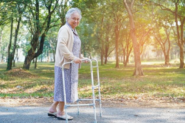 Caminante del uso de la mujer mayor mayor o mayor asiática con salud fuerte mientras que camina en el parque en día de fiesta feliz