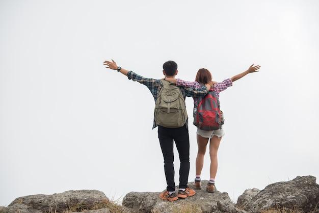 Caminantes pareja con mochilas de pie en la cima de una montaña y disfrutar de la naturaleza ver