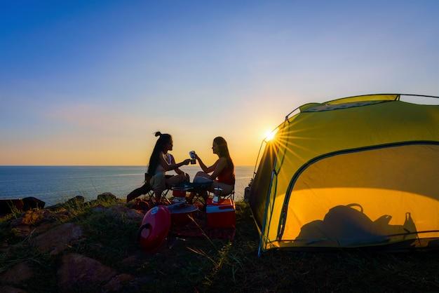 Caminantes que caminan con la mochila en una montaña en la puesta del sol. viajero va de campamento