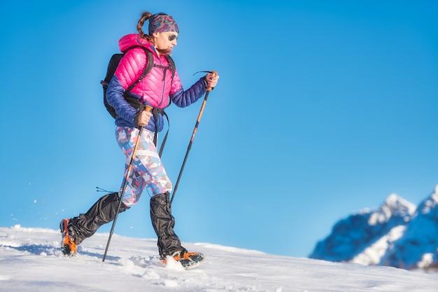Caminata en nieve con crampones ligeros. una mujer joven