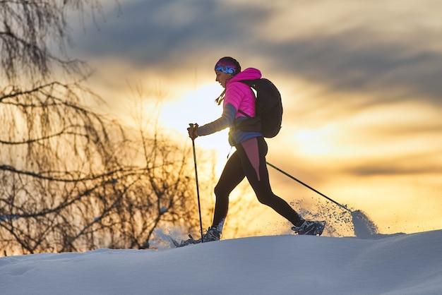 Caminata de niña solitaria con raquetas de nieve al atardecer