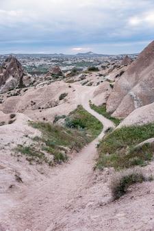 Un camino entre los acantilados rosados de capadocia. turismo y viajes. precioso paisaje. vertical.