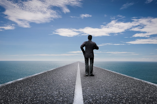 Camino al concepto futuro con vista trasera del empresario de pie en un largo camino