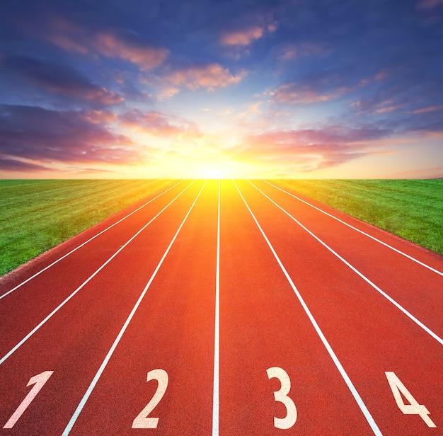 Camino al éxito. concepto de competencia. pista de deporte de atletismo y cielo.