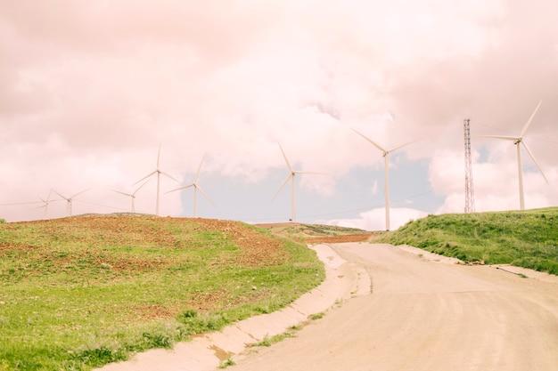Camino por campos con molinos de viento.