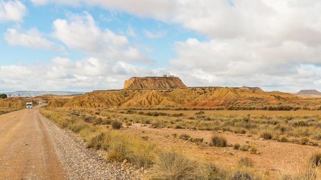 Camino en un desierto con una vista de un monolito bajo un cielo nublado