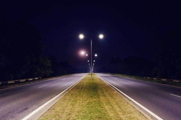 Un camino de dos vías iluminado por la noche.