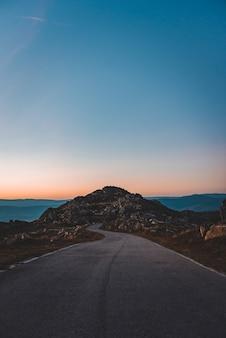 Camino estrecho que conduce a una cueva rocosa bajo el hermoso cielo del atardecer