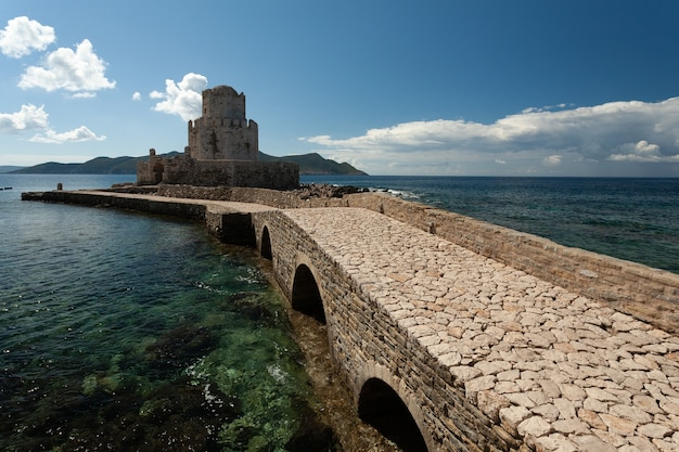 Camino hacia la fortaleza veneciana de methoni bajo un cielo azul en grecia