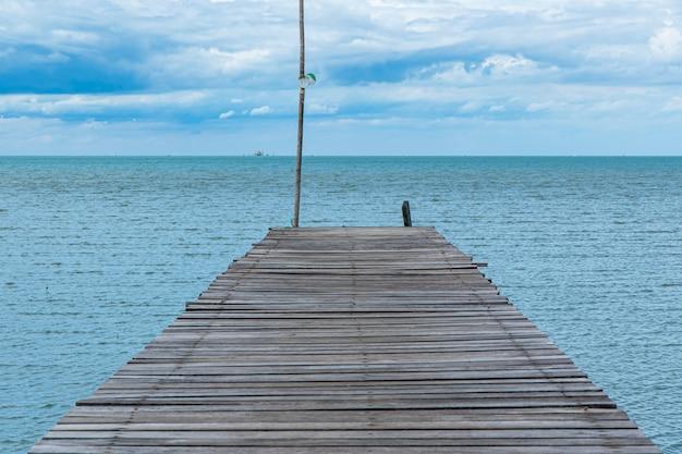 Camino de madera final del mar y cielo azul