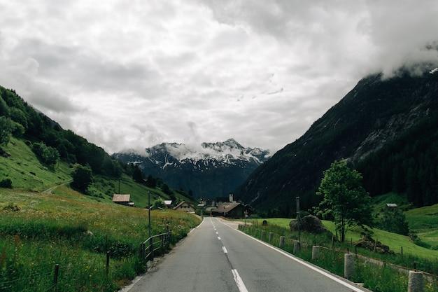 Camino en las montañas de los alpes suizos en clima nublado de verano