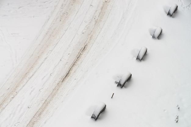 Camino nevado. cercado de ruedas viejas. cerca de los neumáticos.