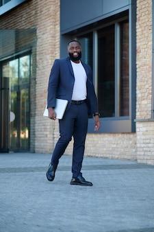 De camino a la oficina. un hombre de piel oscura con traje de camino al trabajo.