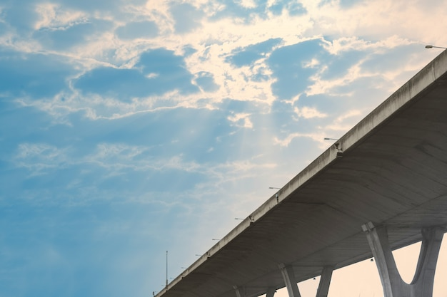 Camino de peaje en el cielo azul con nubes y fugas del rayo de sol, vista inferior, hora del día