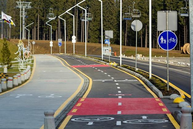 Camino a pie y señales de carril bici en la superficie de la carretera de asfalto