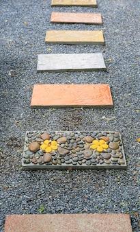 Camino de piedra hermoso en el parque con el fondo de la grava.