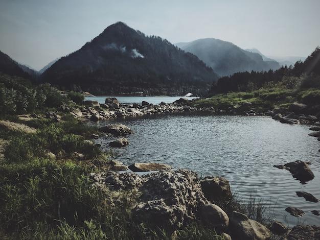 Camino rocoso en medio del agua con una montaña en el fondo