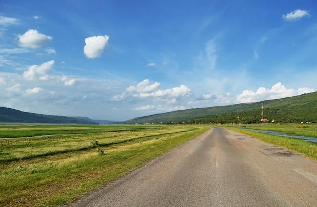 Camino rural hermoso y cielo azul entre el campo rural.