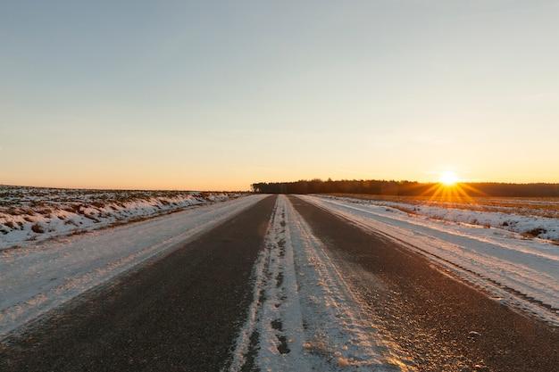 Camino rural bajo la nieve en invierno