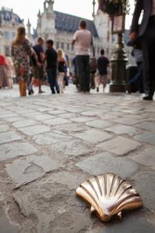 Camino de santiago concha de metal dorado en las calles suelo suelo de piedra con una multitud de personas en la plaza principal de bruselas, bélgica