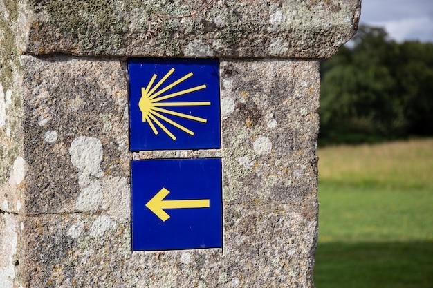 Camino de santiago signo de flecha y vieira amarilla en el antiguo muro de piedra.