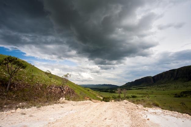 Camino de tierra rural con cielo oscuro de tormenta