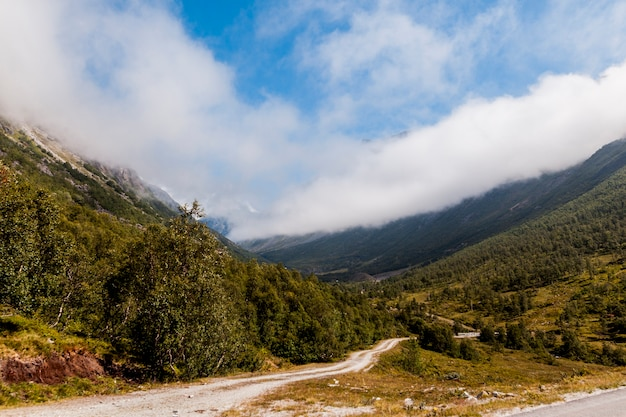 Camino de tierra sinuoso recto en el paisaje de montaña verde