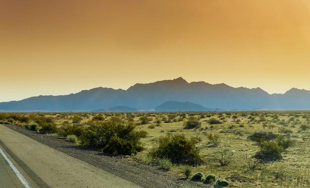 Camino a través del desierto al atardecer